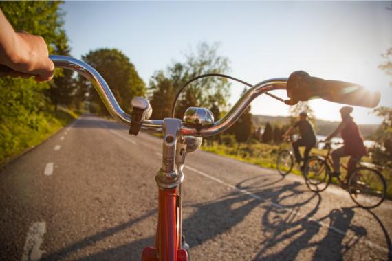 Ett cykelstyre i motljus på en asfaltsväg.