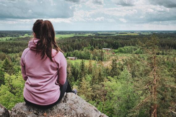 En kvinna med brunt hår i hästsvans och rosa huvtröja sitter på en klippa och tittar ut över utsikten med skog och ängar.