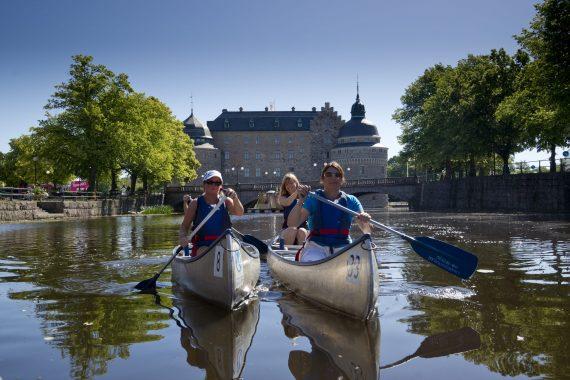 Kanotister paddlar i Svartån med Örebro slott i bakgrunden.