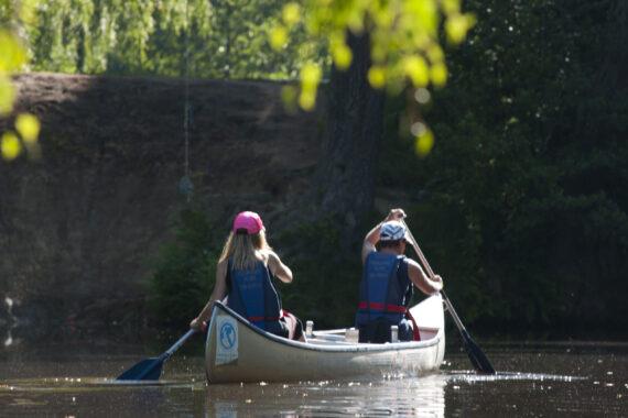 Två kanotister i en silverfärgad kanot-