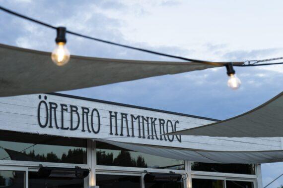 Detalj av ett vitt trähus med skylten Örebro Hamnkrog. Utomhusbelysning och segeldukar hänger framför.