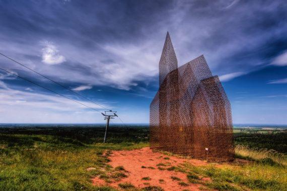 Ett konstverk som liknar en kyrka med torn, tillverkad av ett halvtransparent material. Står på en gräsbeklädd mark och himlen bakom är blå.
