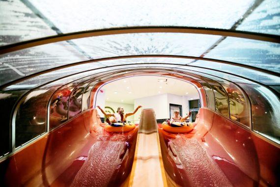 En röd, inglasad rutschkana i ett vattenland som täcks av ett transparent tak.
