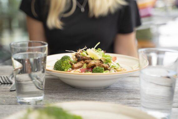 En vit, djup tallrik med kyckling och sallad. Två vattenglas och bestick. I bakgrunden syns en svart tröja och blonda hårslingor.