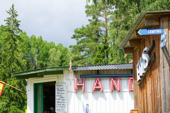 En Konsumbutik med flagga ute och ett träskjul med skylten ELVIS.