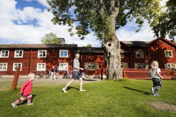 Två små barn och en kvinna springer på gräset i Wadköping.