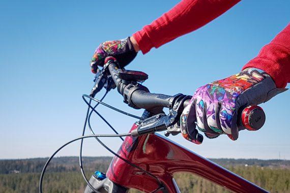 Två mönstrande handskbeklädda händer håller om ett rött cykelstyre.