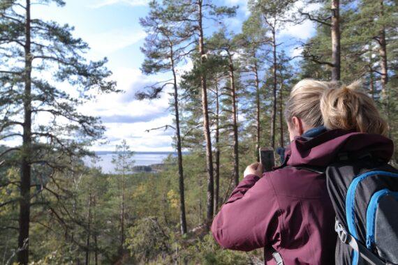 Utsikten mellan tallarna skymtas en sjö. En tjej med blond hästsvans och lila jacka fotar utsikten.
