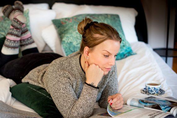 En person ligger på mage i en säng med raggsockor på sig och läser ett magasin.