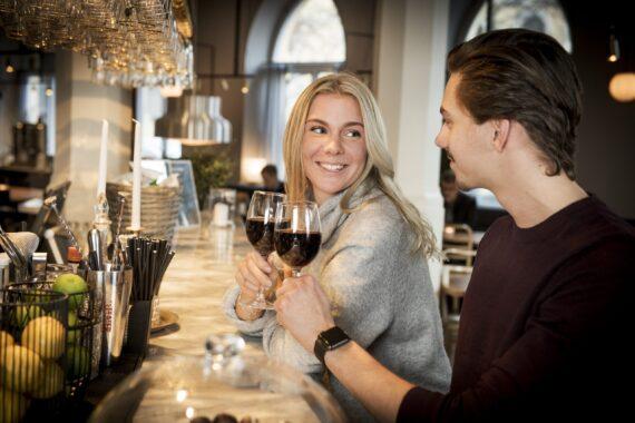 En tjej och en kille sitter i en bar och skålar med rödvin.