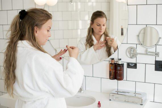 En ljushyad kvinna har en vit morgonrock på sig och målar naglarna. Hon står i ett vitt, kaklat badrum med schackrutigt golv.