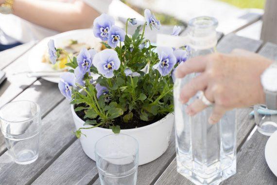 Ett utebord med lila blommor och porslin.