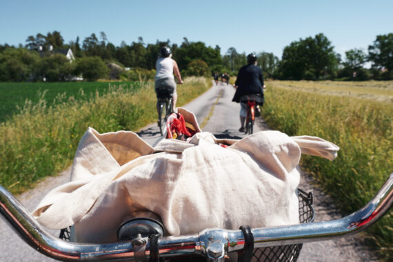 Ett cykelstyre med en vit kasse i korgen. Framför cykel syns en stig där två damer cyklar.