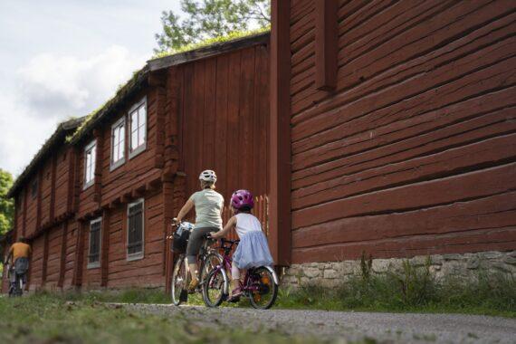 Två röda timmerhus och två cyklister.