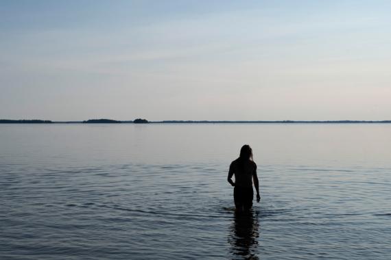En person badar i en spegelblank sjö.