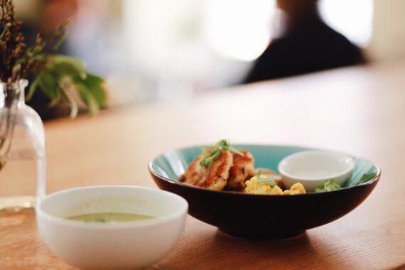 En svart tallrik med blå insida, fylld av vegetariska biffar och en skål sås.