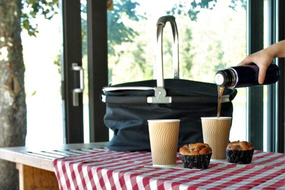 En rödrutig duk och svart picknickväska med två muggar och två bullar.