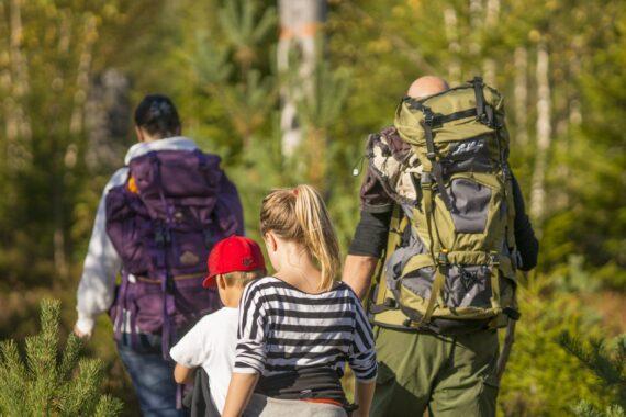 Två vuxna och två barn är ute och går i skogen med ryggsäckar.