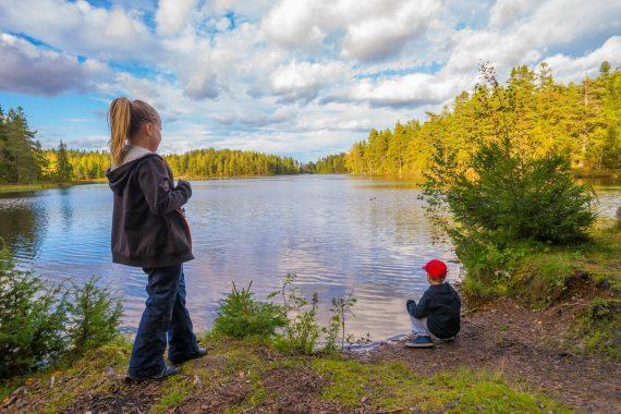 Två barn står och sitter intill en sjö i skogen.