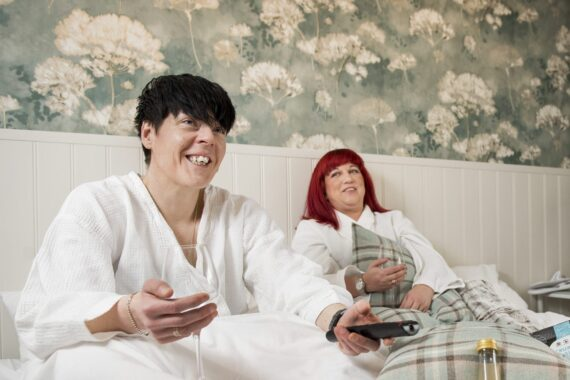 Två kvinnor sitter i en säng med morgonrockar på sig.