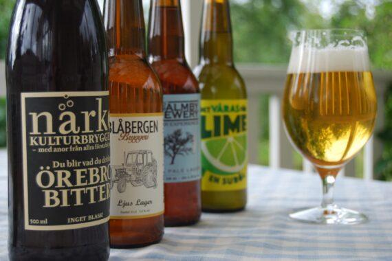 Fyra lokala ölflaskor och ett glas med öl i.