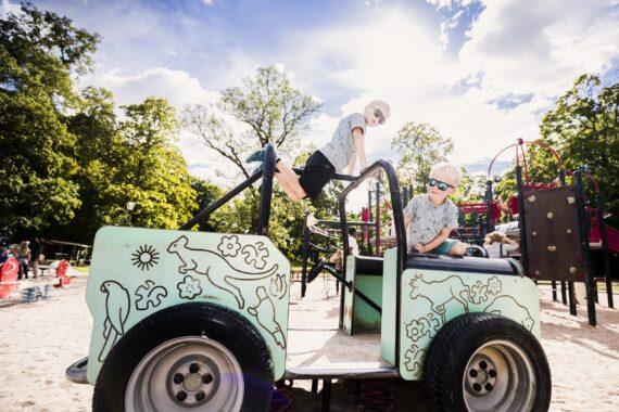 Två blonda barn leker på en turkos leksaksbil.