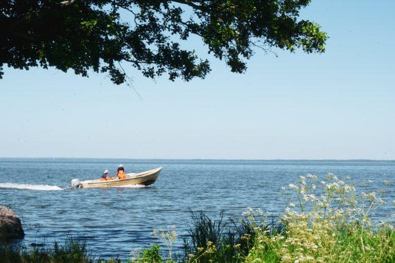 Två fiskare med orange byxor åker i en liten eka på sjön.