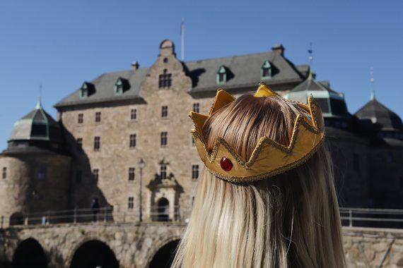 En tjej med krona i tyg står framför Örebro slott.