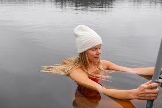 Närbild på Annika Harrsjö som vinterbadar med vit mössa och röd baddräkt.