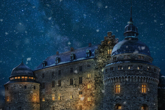 Örebro slott med snöfall och mörkblå himmel.