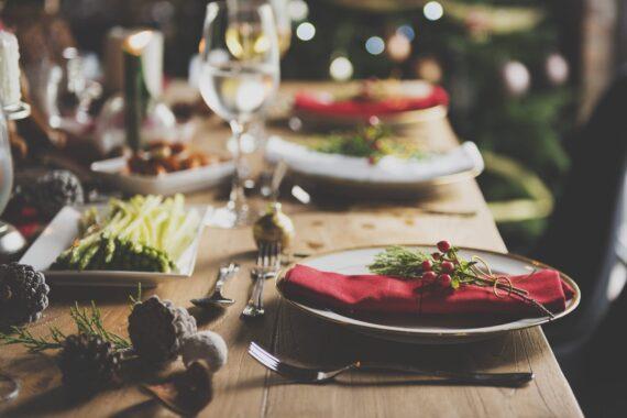 Ett juldekorerat matbord med röda servetter och gröna kvistar.