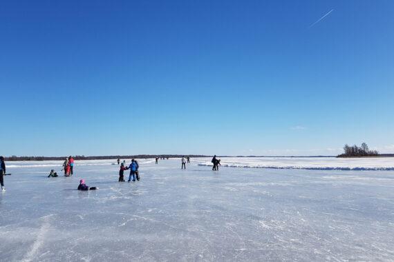 Spegelblank is på en sjö och blå himmel.