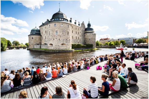 Många människor sitter på soldäcket framför Örebro slott.