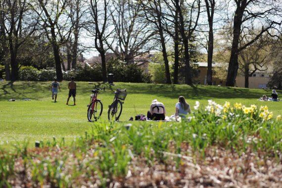 Två personer sitter på gräset och en cykel står parkerad intill.