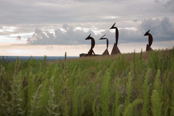 Fyra statyer i brun färg syns på höll mellan grässtrån.