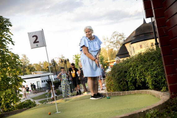En äldre kvinna i ljusblå klänning spelar minigolf och ska precis putta bollen mot hålet.
