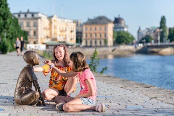 Två barn med långt hår sitter framför en staty av ett sittande barn.