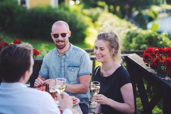 Tre personer sitter på en uteservering och dricker vitt vin.