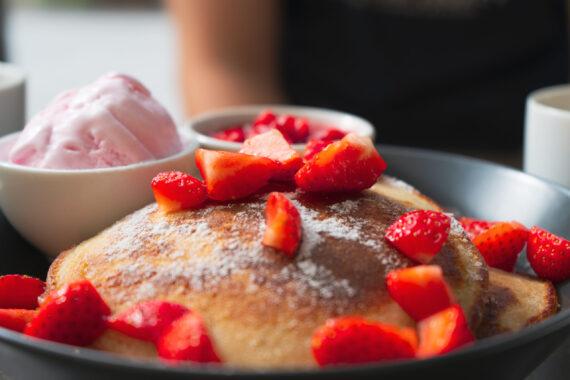 En tallrik med pannkakor, jordgubbar och jordgubbsglass.